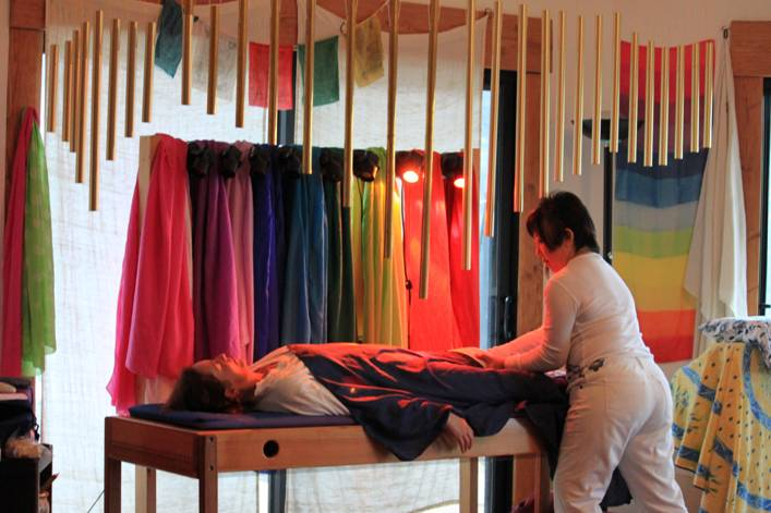 Pat Aoki, Tama-Do Practitioner, works on a client with the Tama-Do Rainbow Silks and Chakra Lights® for the TEP®